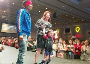 Logan Parker walks with his mom at the CMN Conference