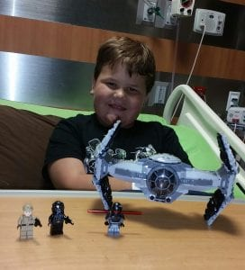 Luke Edmunds plays with Star Wars toys in the hospital